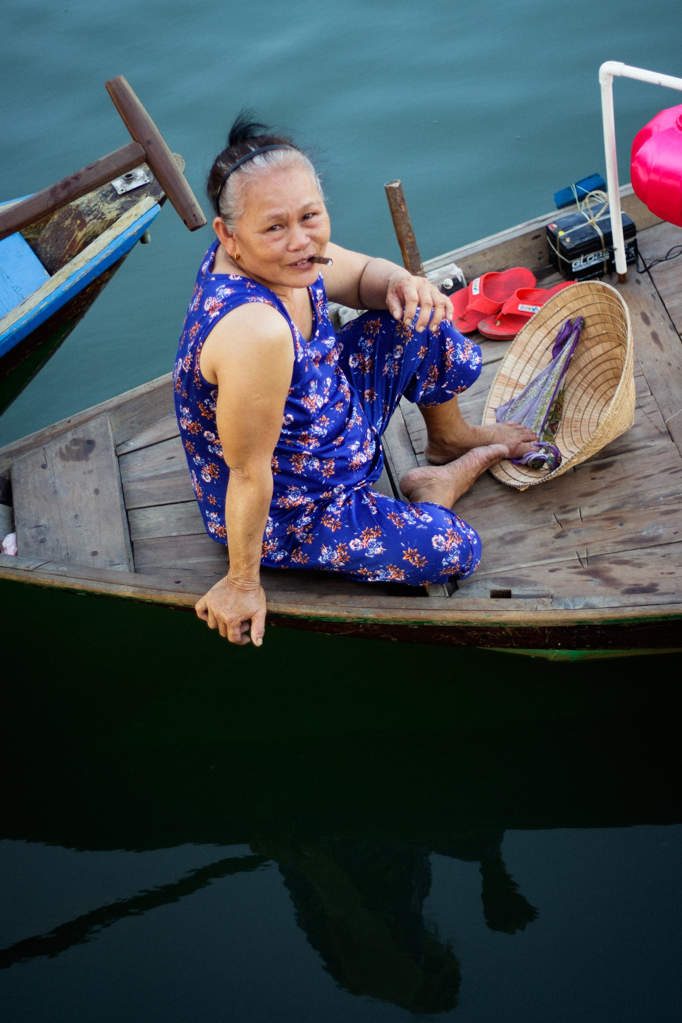 A boat woman smiles as she notices the camera.