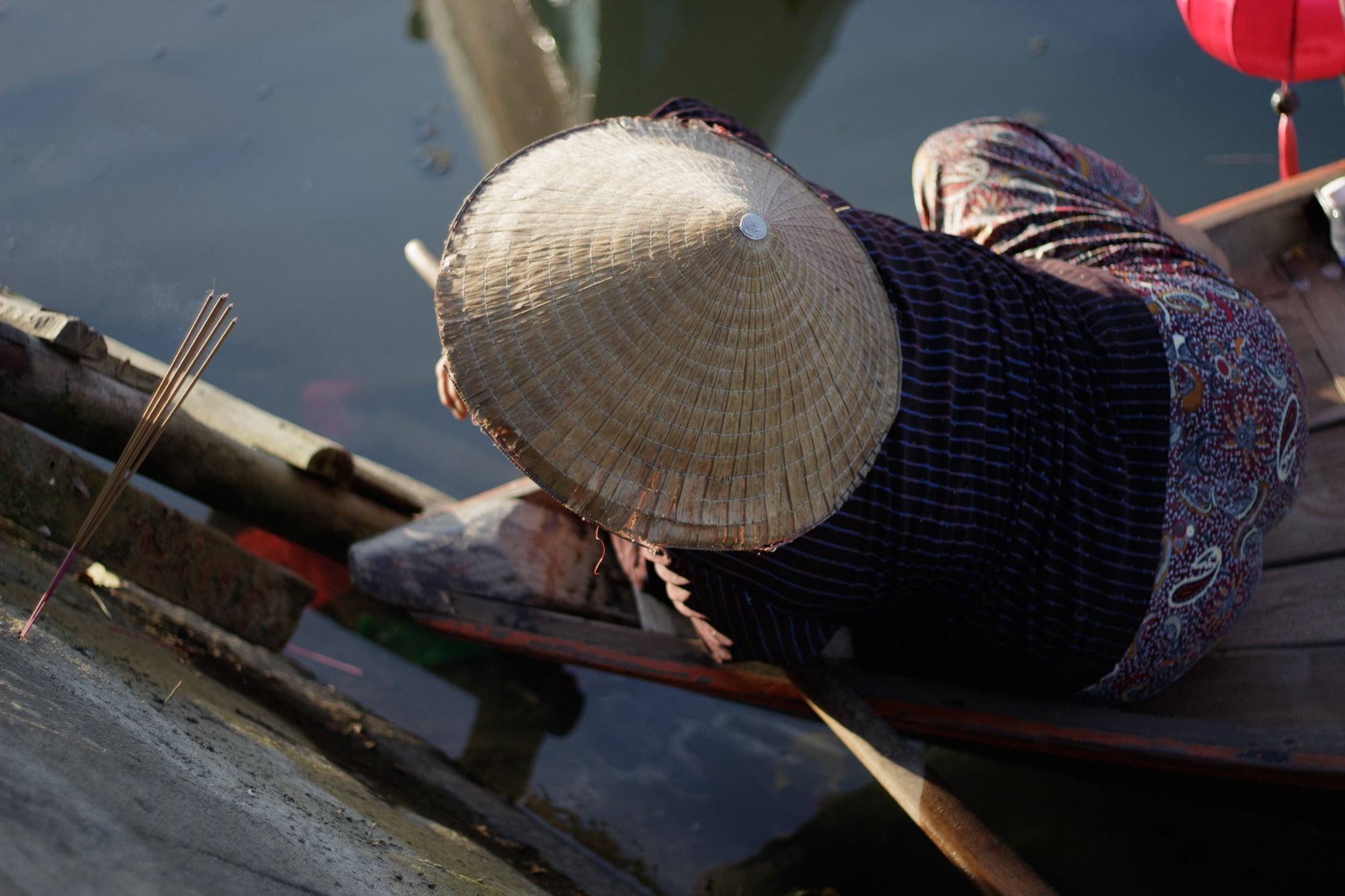 A boat woman photographed as she lights incense sticks.
