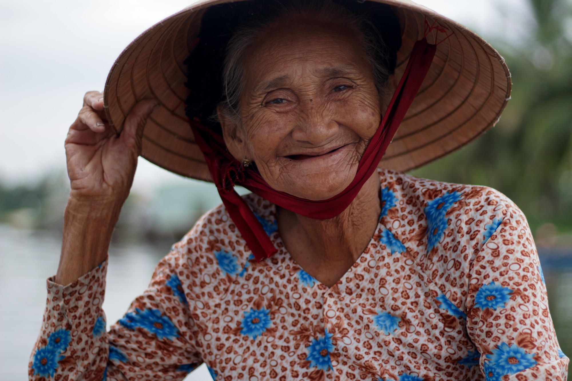 An elderly boat woman in Hoi An smiles as she is pictured during a boat ride.