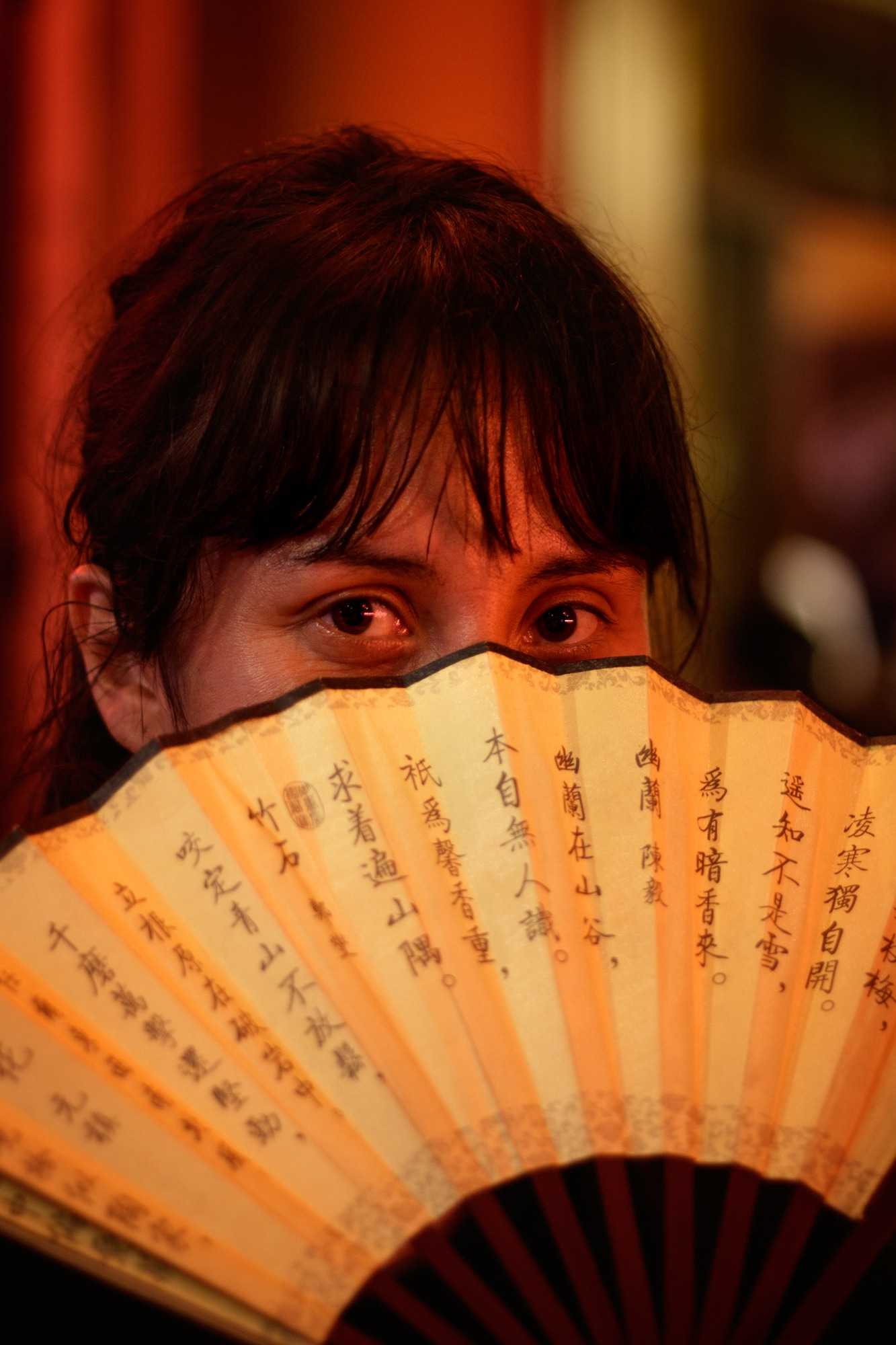 A tourist covers her face with a hand held fan at a restaurant in Hoi An.