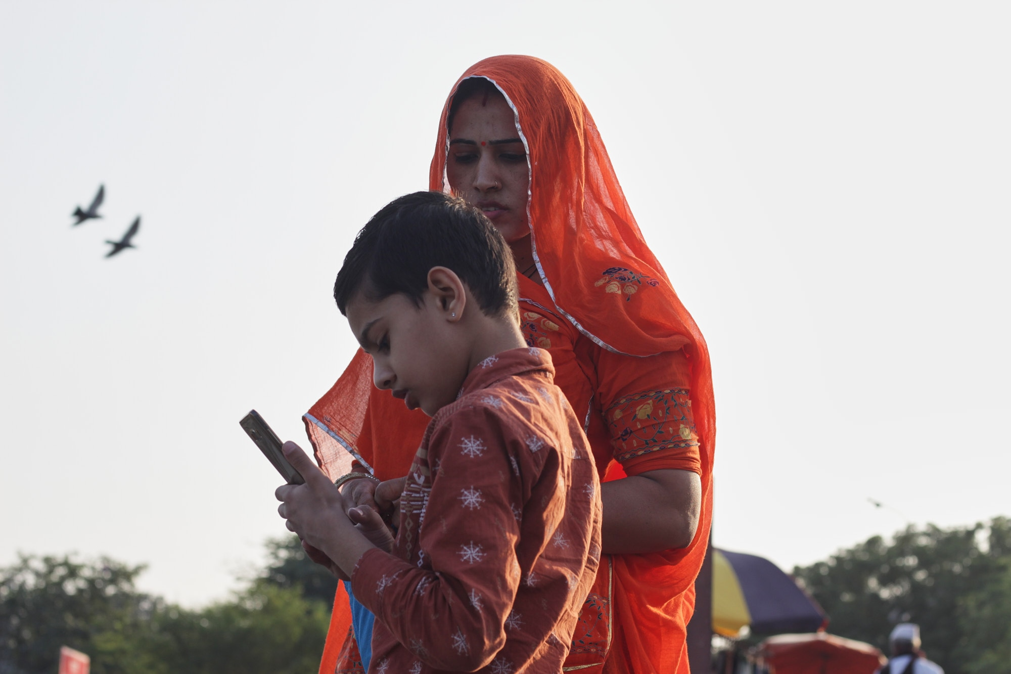 A boy helps his mother with a cellphone