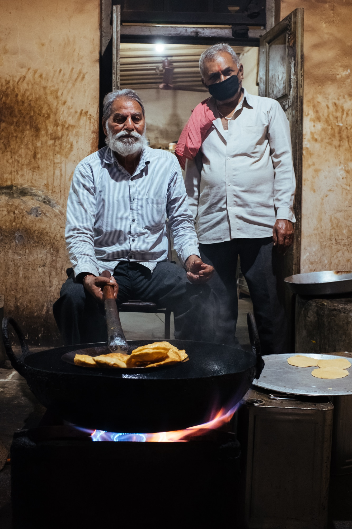 A man at Jalaram Temple in Ahmedabad fries puris as 'maharaj' or the head chef observes.