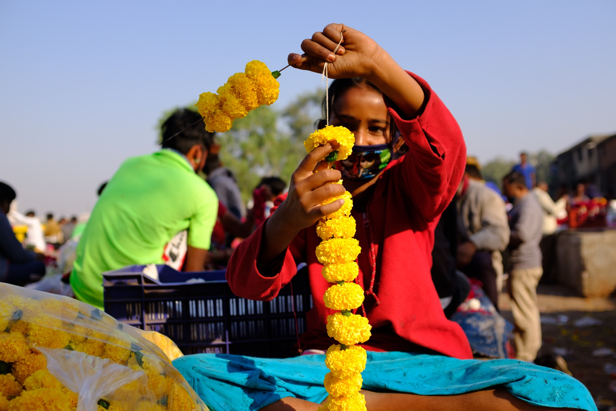 A young girl working at a flower market in Ahmedabad.