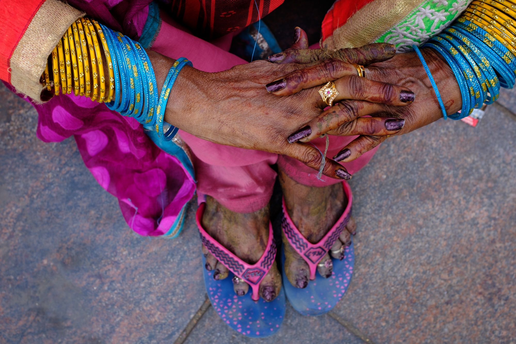 Henna-painted hands of a woman wearing colourful bangles. Ahmedabad.