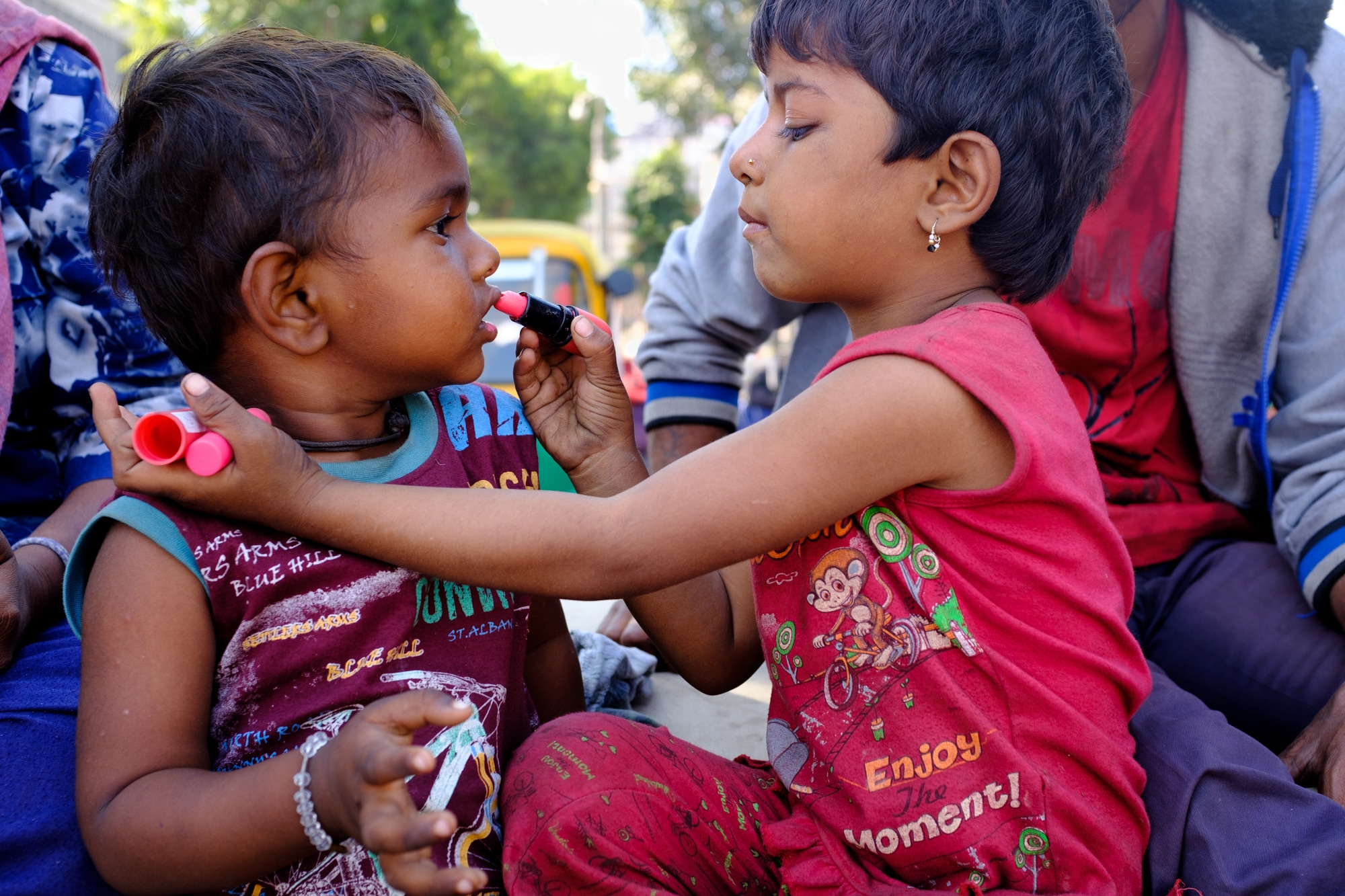 A girl applies lipstick to her brother's lips. Ahmedabad.