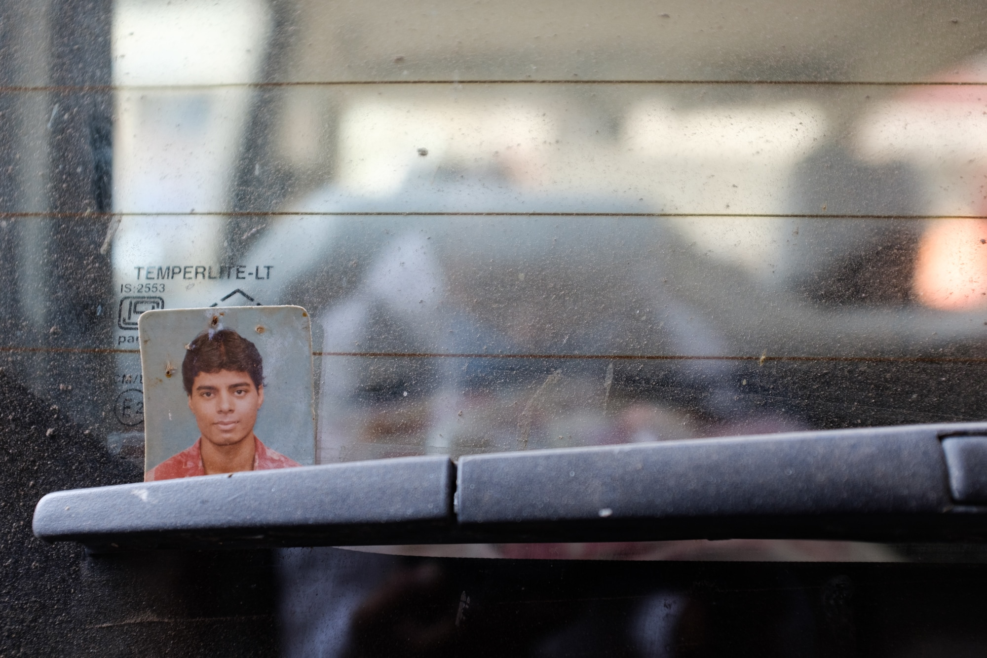 An old passport size picture at the back of a car.