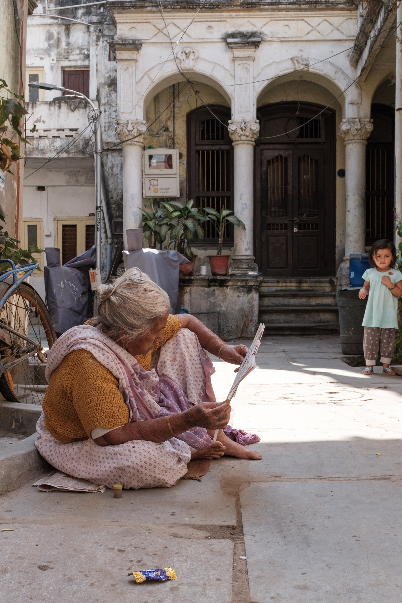 An elderly woman in her eighties reading newspaper near her house in a pole in Ahmedabad.