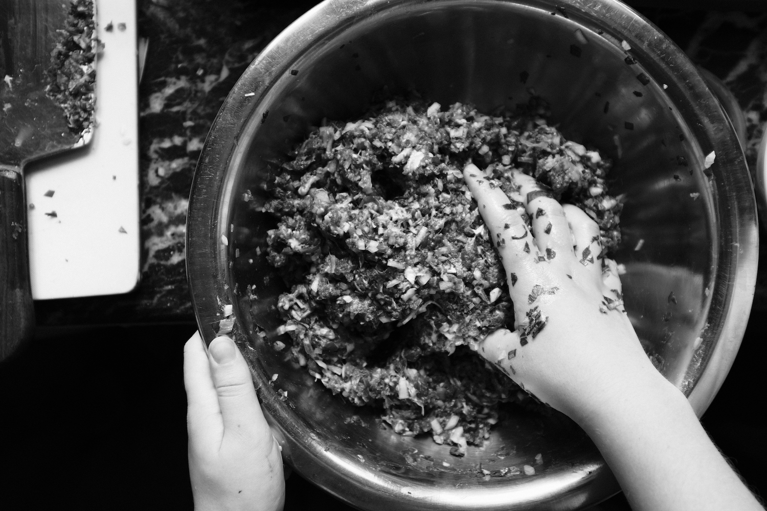 Minced meat and vegetables being mixed for momos