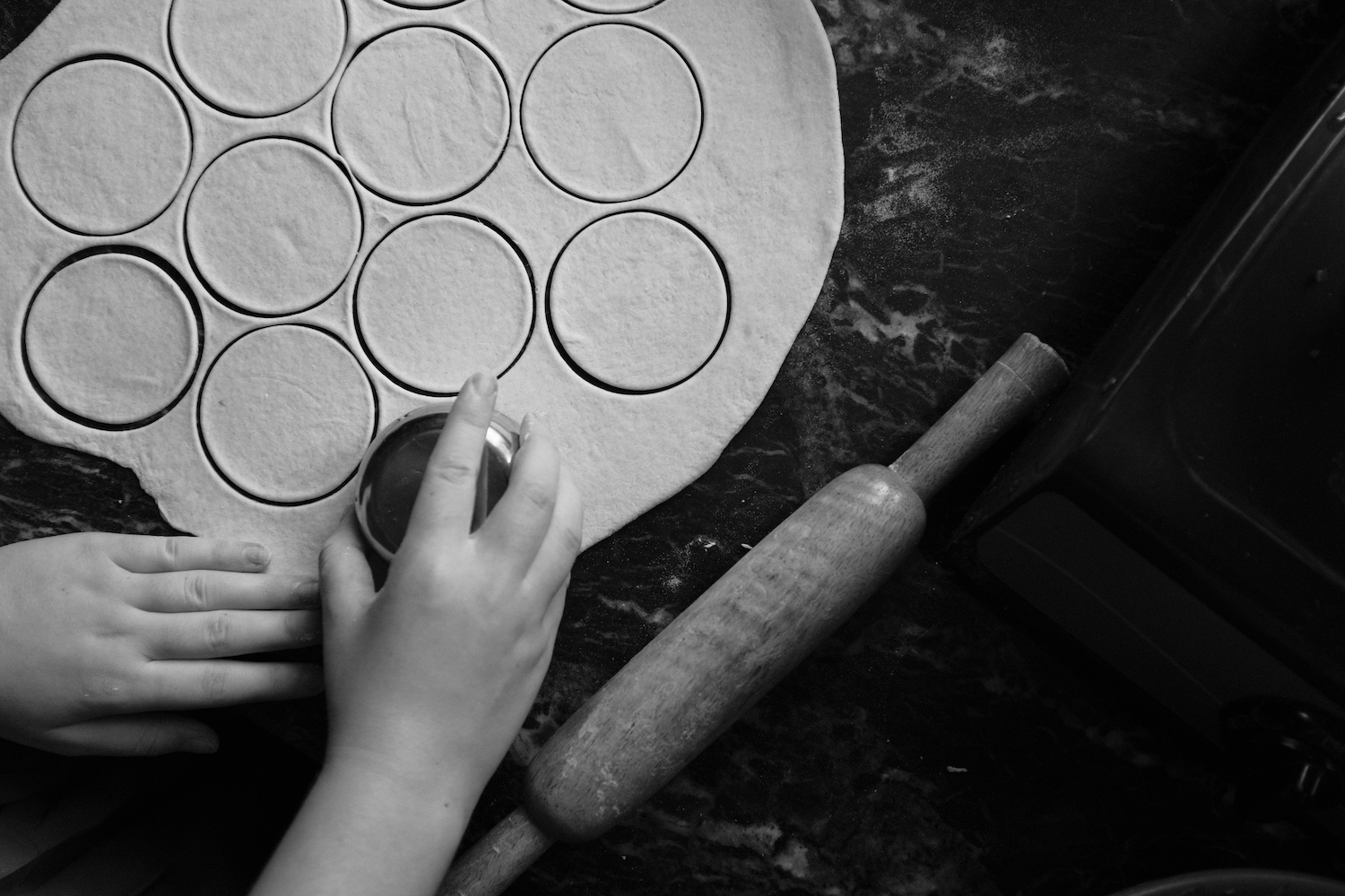 Rolled dough being cut into round shape using a small metal bowl