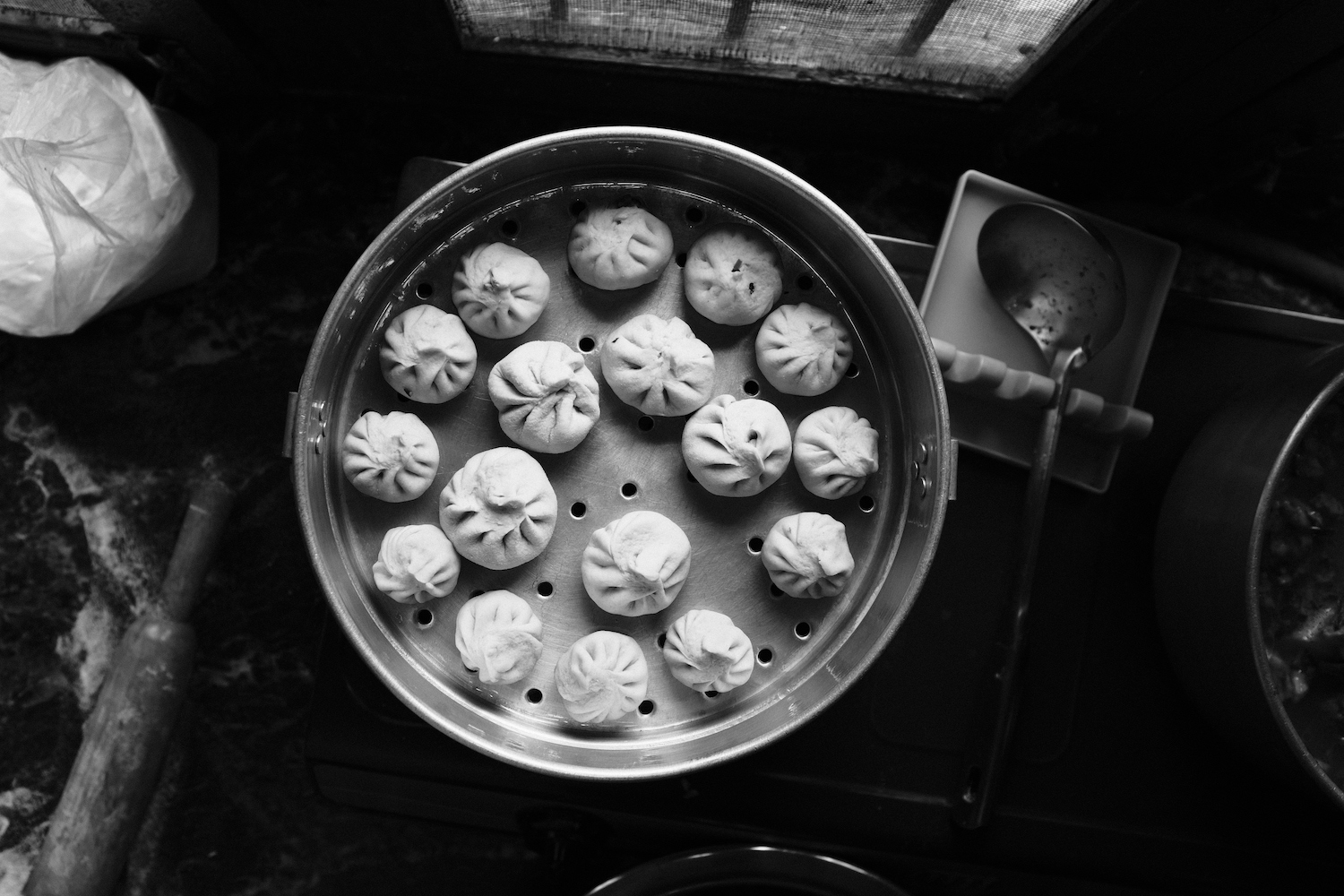 Uncooked momos sitting in the steamer
