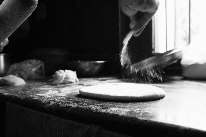Thupten sprinkling flour as he rolls the dough
