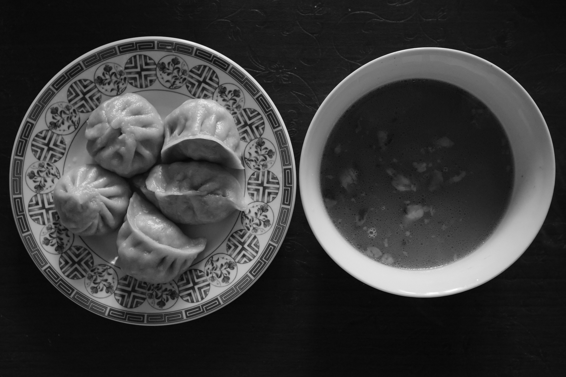 A plate of momos and a bowl of soup