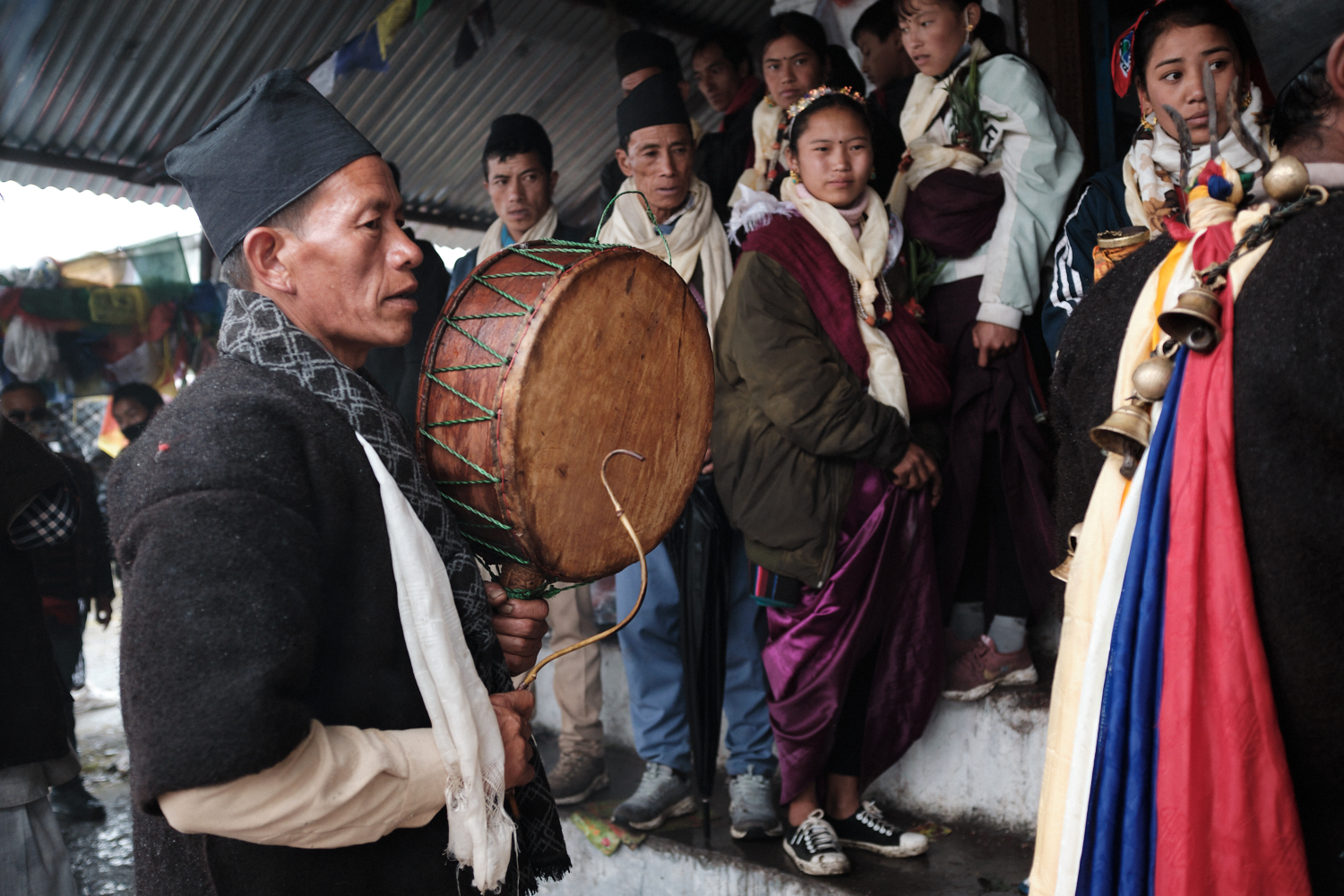 A shaman playing 'dhyangro' drum as other observe the ceremony