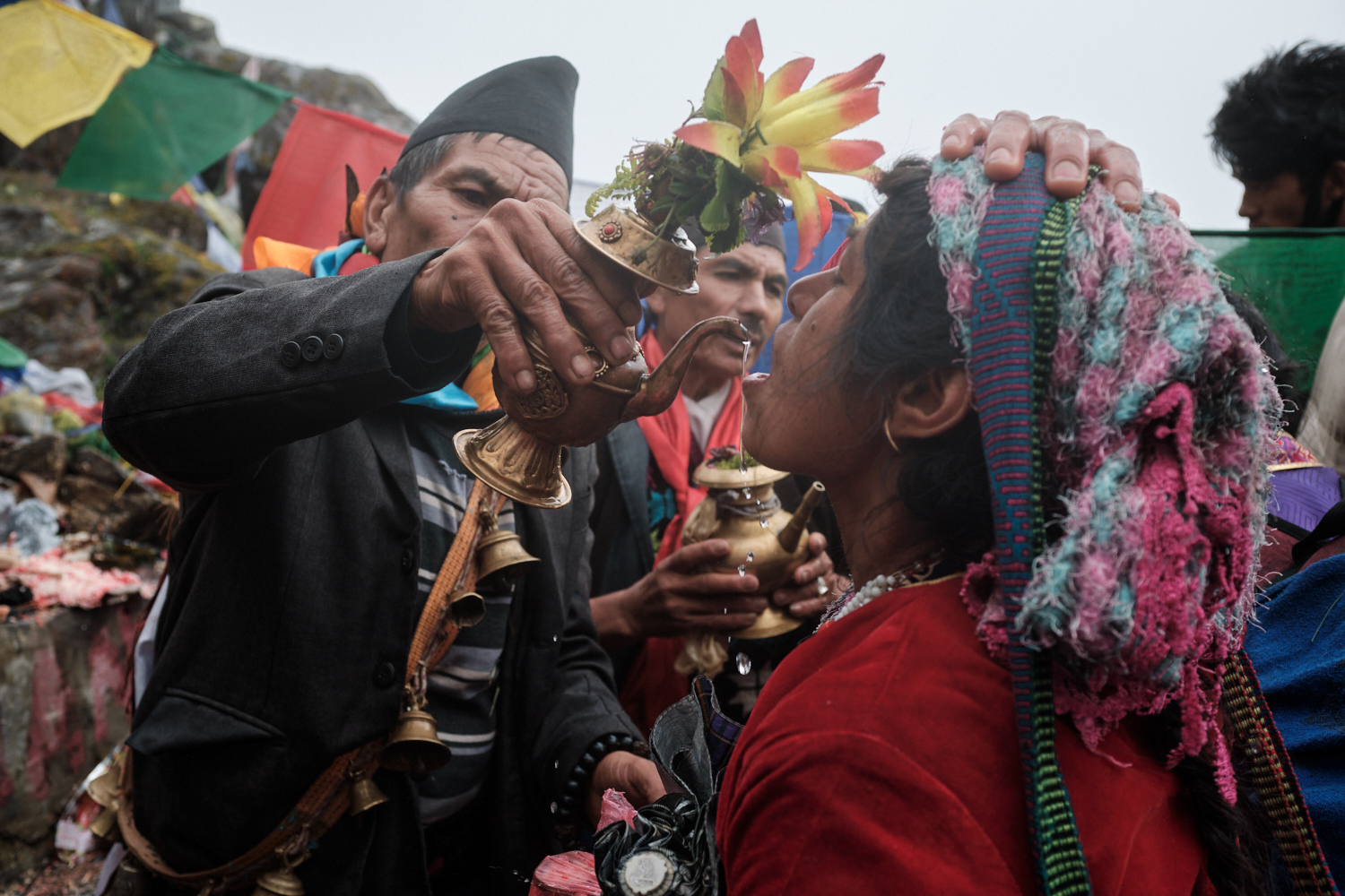 A woman receives holy water from Trishul Dhara by the hands of a shaman